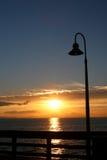 заход солнца столба пристани светильника Стоковая Фотография