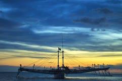 Заход солнца с взглядами шлюпки на пляже стоковая фотография rf