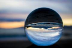Заход солнца с красочным небом с океаном и островом в стеклянном шарике Стоковое фото RF