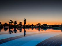 Заход солнца с ладонью silhuettes и отражение в бассейне стоковое фото rf