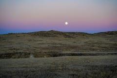 Заход солнца с луной и восход луны на высоких равнинах пустыни стоковая фотография rf