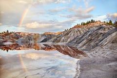 Заход солнца с радугой в холмах песка Земли сказки волшебные стоковое изображение