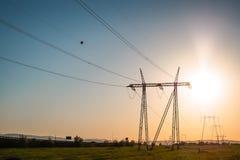Заход солнца с электрическими штендерами, решеткой и производством электроэнергии стоковые изображения