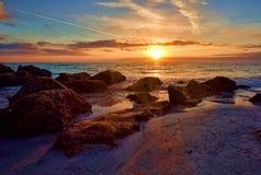 Заход солнца с Sunburst над скалистым Seashore Стоковые Фотографии RF