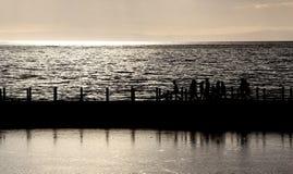 заход солнца silhouetted людьми Стоковая Фотография