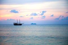 заход солнца silhouetted шлюпкой Стоковые Фото