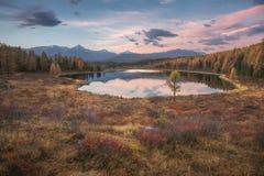 Захода солнца озера зеркал ландшафт осени поверхностного предыдущего широкоформатный с горной цепью на предпосылке Стоковое Изображение RF
