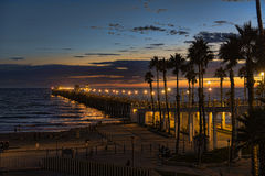 Заход солнца на пристани берега океана Стоковая Фотография
