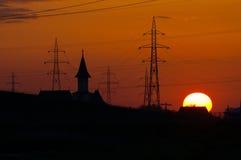 Заход солнца, башня церков и электрические поляки стоковая фотография rf