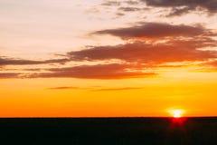 Заход солнца, восход солнца над сельским пшеничным полем Яркое драматическое небо и Стоковые Изображения