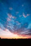 Заход солнца, восход солнца над сельским лугом поля Яркое драматическое небо Стоковая Фотография RF