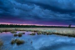 Заход солнца во время шторма над болотом Стоковые Изображения RF