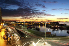 Заход солнца в гавани города Виго с автомобилями освещает в движении стоковое фото