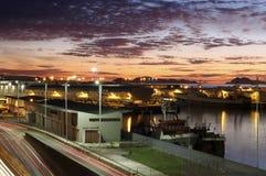 Заход солнца в гавани города Виго с автомобилями освещает в движении стоковая фотография