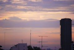 Заход солнца в городе с сладостным фиолетовым розовым небом Стоковые Фото