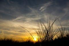 Заход солнца в песчанных дюнах на пляже Стоковые Фото