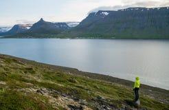Заход солнца девушки наблюдая над фьордом в западной Исландии Стоковые Изображения