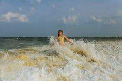 Заход солнца девушки серфера наблюдая на surboard плавая в зеленый голубой океан Стоковое Фото