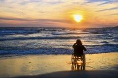 Заход солнца, делает sightseeing на пляже женщину на кресло-коляске стоковое изображение