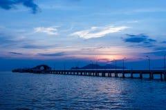 Заход солнца за малыми кораблем порта и столбом лампы Стоковая Фотография