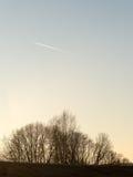 Заход солнца зимы с луной и самолетом отстает в небе Стоковое Фото