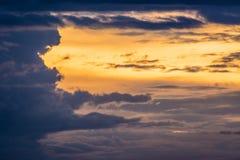 Заход солнца, золотая предпосылка неба и черные тучи Стоковое Изображение RF