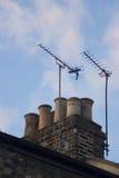 Заход солнца здания крыши печной трубы антенны ТВ arial Стоковые Изображения RF