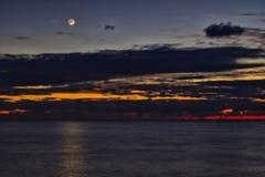 Заход солнца и молодой месяц Стоковое Фото