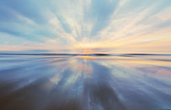 Заход солнца и отражение пастельного цвета на песке с небольшой нерезкостью сигнала стоковая фотография rf