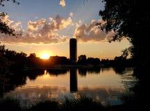 Заход солнца и силуэт городка с отражением в воде Стоковое фото RF