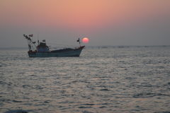 Заход солнца и шлюпка Стоковое Изображение