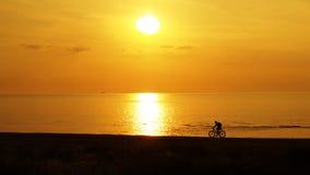 Заход солнца и cyclis на морском побережье Стоковые Изображения