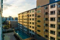 Заход солнца кондоминиума с квартирами нового блока плавательного бассеина современными Стоковые Фото