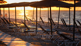 Заход солнца моря лета среди loungers солнца и зонтиков пляжа соломы, Греции, Родоса Стоковая Фотография