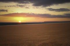 Заход солнца моря и коричневые облака поля и апельсина Стоковое Фото