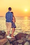 Заход солнца молодых пар наблюдая в заднем взгляде Стоковое Изображение