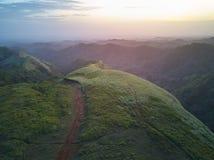 Заход солнца над ландшафтом зеленых холмов Стоковые Изображения RF