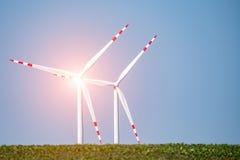 Заход солнца над ветрянками на поле Стоковое Изображение