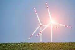 Заход солнца над ветрянками на поле Стоковая Фотография