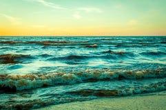 Заход солнца на взморье с волнами Стоковые Изображения RF