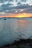 Заход солнца над водой с шлюпкой Стоковая Фотография RF