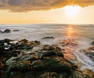 Заход солнца на вулканическом пляже камней hawaii стоковые изображения rf
