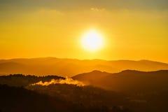 Заход солнца над горами с дымом от дома Стоковые Изображения RF