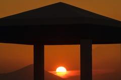Заход солнца на деревне Kalamos в Греции Солнце обрамлено через столбцы здания стоковые изображения rf