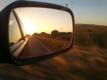 Заход солнца на зеркале автомобиля Стоковые Фотографии RF