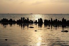 Заход солнца на камнях моря в воде Стоковая Фотография RF