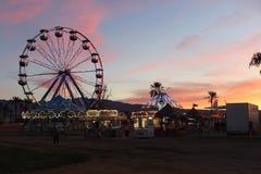 Заход солнца над колесом Ferris и ездами масленицы стоковые фотографии rf