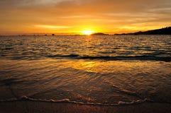 Заход солнца на красивом пляже с волнами, там шлюпки и mo Стоковые Фото