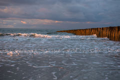 Заход солнца на кучах на пляже Северного моря Cadzand, Голландии Стоковое Изображение