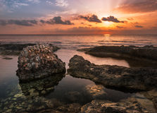 Заход солнца над морем и скалистым побережьем с старыми руинами Стоковое Изображение